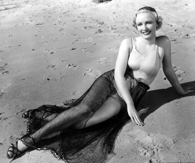 Wearing a satin and lastex top and a skirt made of fishnet Ann Evors, a Paramount player,  poses for the cameramen on the beach, circa 1928.  (Photo by Central Press)