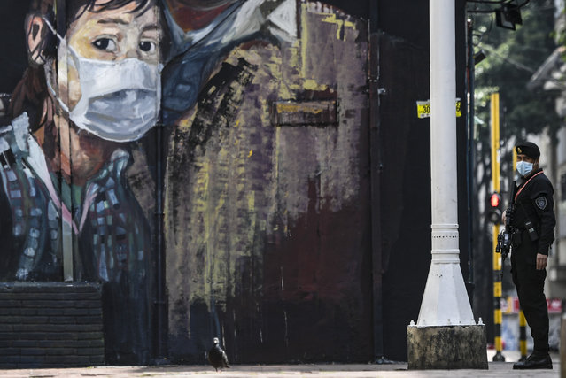 A member of the special forces police wears a face mask against the spread of the new coronavirus as he stands guard in front of a mural depicting a person wearing a face mask in Bogota on March 21, 2020. Colombian President Ivan Duque announced mandatory preventive isolation from March 24 to April 13 as a measure against the spread of the novel coronavirus. (Photo by Juan Barreto/AFP Photo)