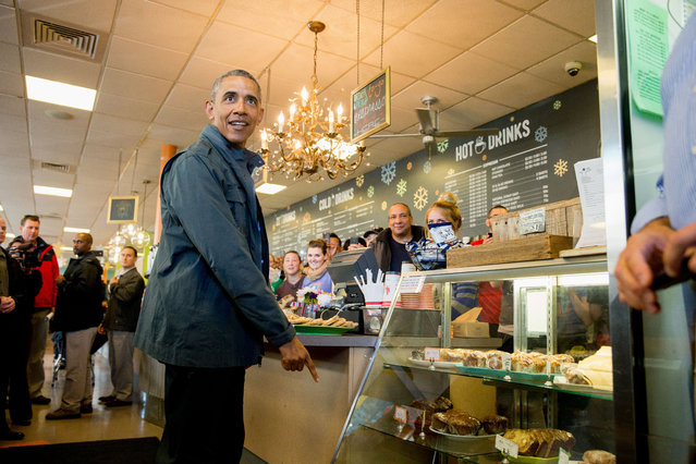 President Barack Obama points to a pastry display at the Snow City Cafe in Anchorage, Alaska, Tuesday, September 1, 2015. Obama is on a historic three-day trip to Alaska aimed at showing solidarity with a state often overlooked by Washington, while using its glorious but changing landscape as an urgent call to action on climate change. (Photo by Andrew Harnik/AP Photo)
