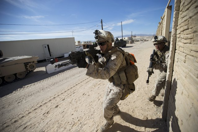 U.S. Marines from Fox Company, 2nd Battalion 1st Marines, 13th Marine Expeditionary Unit move ahead to clear a structure during a non-live fire Military Operations in Urban Terrain (MOUT) training at US Marine Corps: Marines Air Ground Combat Center in Twentynine Palms, California September 1, 2015. (Photo by Mario Anzuoni/Reuters)