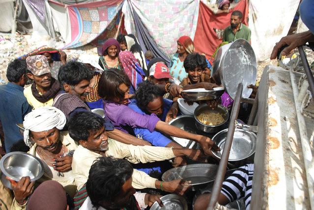 People confined in their homes due to lockdown to contain the coronavirus outbreak jostle to receive free food, in Hyderabad, Pakistan, Wednesday, March 25, 2020. (Photo by Pervez Masih/AP Photo)