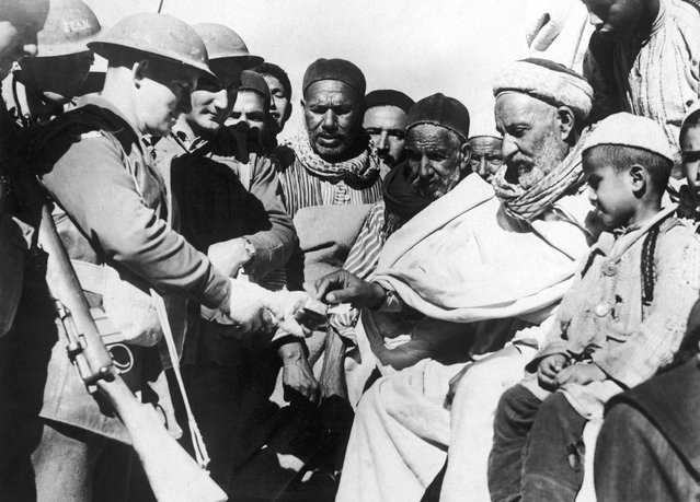 Local people accept gifts from troops during the British occupation of Darnah, Libya during the North African campaign of World War II, 28th February 1941. (Photo by Keystone)