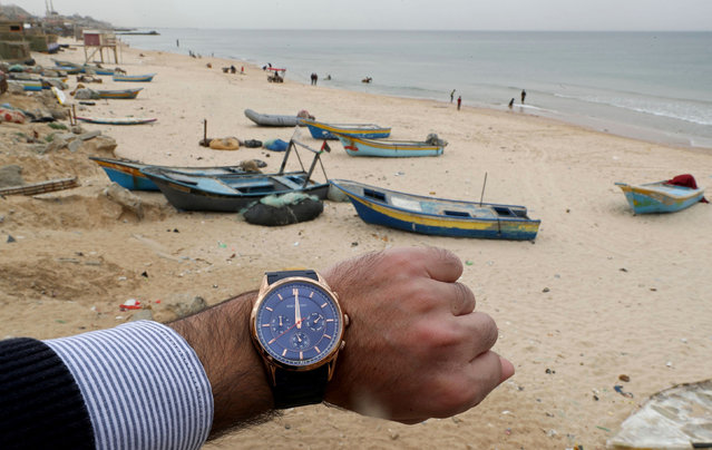 A watch showing the time at noon, is displayed for a photo in front of a beach during the coronavirus disease (COVID-19) outbreak, in the northern Gaza Strip, Palestinian Territories, March 31, 2020. (Photo by Mohammed Salem/Reuters)