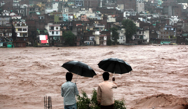 Indian residents look on towards threatened houses as waters from the overflowing Tawi river rage past in Jammu on September 6, 2014. Incessant rains and flooding across northern India has left more than 100 dead across the states of Punjab and Jammu and Kashmir, with thousands marooned in the Himalayan region, officials said. (Photo by AFP Photo)