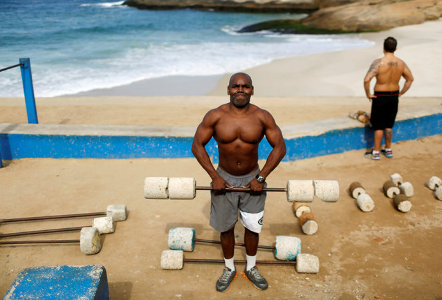 """Marcos Da Costa, 46-year-old, poses as he works out at the Arpoador beach in Rio de Janeiro, Brazil, June 24, 2016. When he asked if he had bought tickets for the Olympics he said, """"I don't agree with the Olympics while people in Rio suffer violence, bad health services, insecurity and construction works like the poorly-designed cycle path"""". (Photo by Pilar Olivares/Reuters)"""