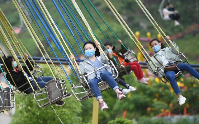 People wearing face masks while using the recreation facilities at a scenic park on April 25, 2020 in Chongqing, China. (Photo by Chen Chao/China News Service via Getty Images)