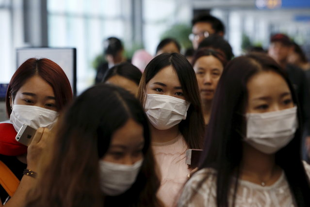 Passengers wearing masks to prevent contracting MERS walk past a thermal imaging camera (unseen) at Incheon International Airport in Incheon, South Korea, June 2, 2015. (Photo by Kim Hong-Ji/Reuters)