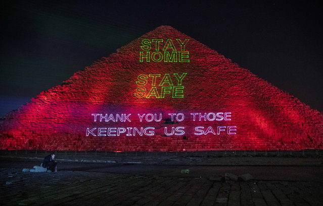 A journalist looks at his mobile phone as the Ministry of Antiquities lights up the pyramids in an expression of support for health workers battling the coronavirus outbreak, Monday, March 30, 2020, in Giza, Egypt. (Photo by Nariman El-Mofty/AP Photo)