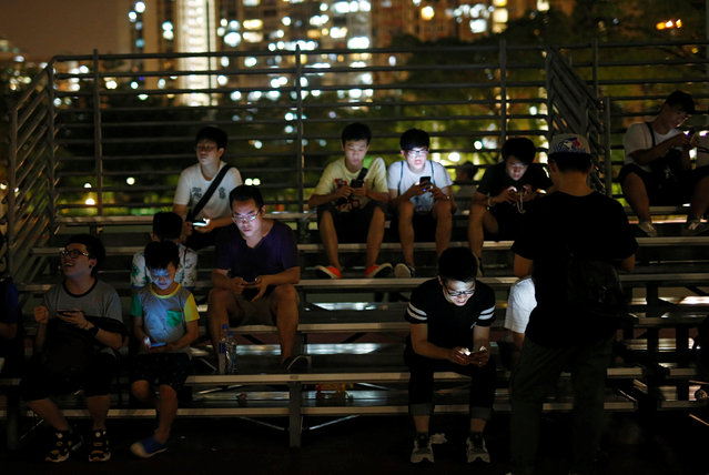 "People play the augmented reality mobile game ""Pokemon Go"" by Nintendo in Hong Kong, China August 6, 2016. (Photo by Tyrone Siu/Reuters)"