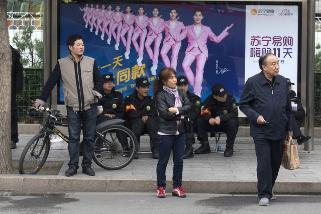 In this Saturday, October 21, 2017 photo, residents wait near security personnel resting near a billboard featuring a popular actor in Beijing, China. (Photo by Ng Han Guan/AP Photo)