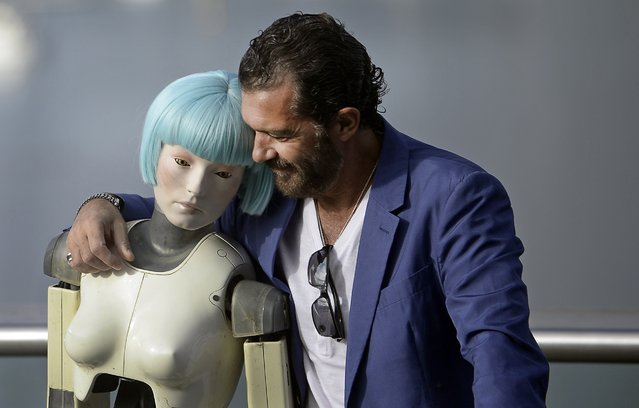 Spanish actor Antonio Banderas embraces a robot used in the film Automata during a photocall on the third day of the 62nd San Sebastian Film Festival, September 21, 2014. Banderas stars in and produced the science fiction film, which is part of the festival's official section. (Photo by Vincent West/Reuters)
