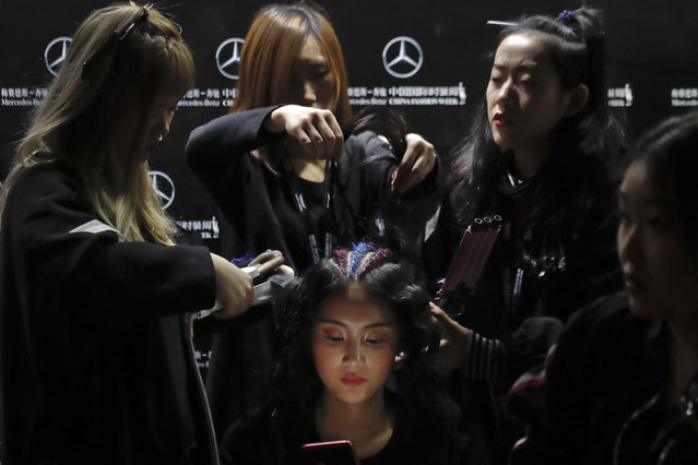 Hairstylists put the final touch on a model's hair backstage to present M.X collection by Chinese designer Yang Shan during the China Fashion Week in Beijing, Wednesday, November 1, 2017. (Photo by Andy Wong/AP Photo)
