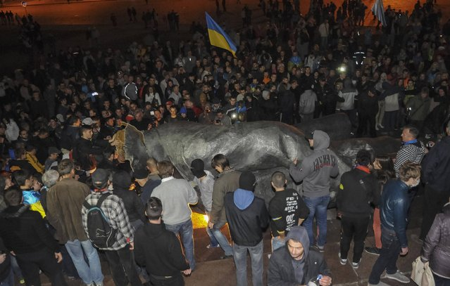 People surround a statue of Soviet state founder Vladimir Lenin (C), which was toppled by protesters during a rally organized by pro-Ukraine supporters in the centre of the eastern Ukrainian town of Kharkiv September 28, 2014. (Photo by Reuters/Stringer)