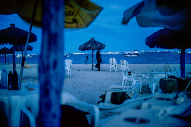 """Salvador, Bahia. """"Where is she going? I liked shooting with virtually no light, even with Velvia film ISO 50 as here. Using a beer bottle as a tripod, I made a few images of my friend Raquel long after the sun had set. Bahia is magic. Bahia is key in the history of Brazil. The first Africans were brought to the continent in the bay in this photograph"""". (Photo by David Alan Harvey/The Guardian)"""