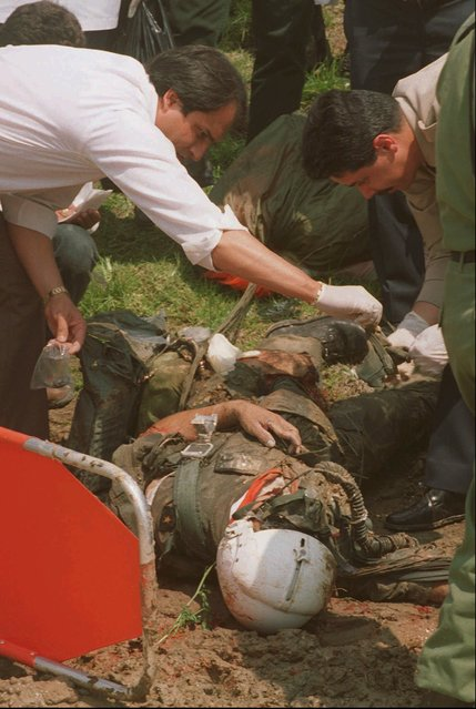 Mexican investigators examine the body of one of three crewmen confirmed dead at the scene of a multiple plane crash Saturday, September 16, 1995 in Cuajimalpa, Mexico, a Mexico City suburb. Three jet fighters, two T-33's and an F-5 of the Mexican Air Force crashed in a canyon outside of Mexico City while taking part in an overflight above Mexico's Independence Day parade. (Photo by Jose Luis Magana/AP Photo)