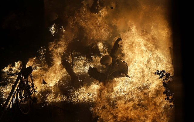 A police officer is engulfed by flames from a petrol bomb thrown by protesters in front of the parliament during clashes in Athens, November 7, 2012. Lawmakers in Greece  backed a new round of austerity measures, despite violent protests across the country. (Photo by Dimitri Messinis/Associated Press)
