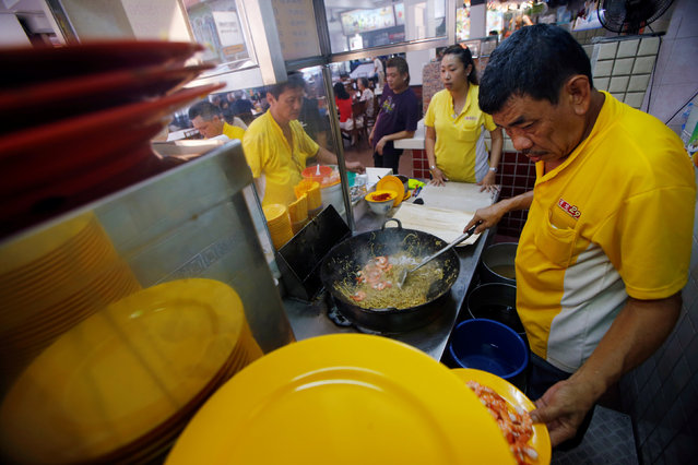 """Hawker Alex See, 66, and his daughter Penny See, 33, cooking at their Geylang Lorong 29 Fried Hokkien Mee stall at East Coast Road in Singapore August 10, 2016. """"Young people come and go, they are not serious about learning. When I was helping my father at the age of 16, I asked him so many questions everyday to learn so that I can one day beat him at it. I do not think I have beaten my old man yet, it's a tie"""", See said. (Photo by Edgar Su/Reuters)"""