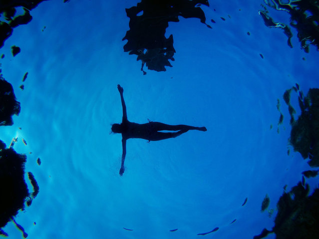 In this underwater picture a woman floats in a swimming pool during a summer day in Madrid, Spain, Sunday, August 28, 2016. (Photo by Daniel Ochoa de Olza/AP Photo)