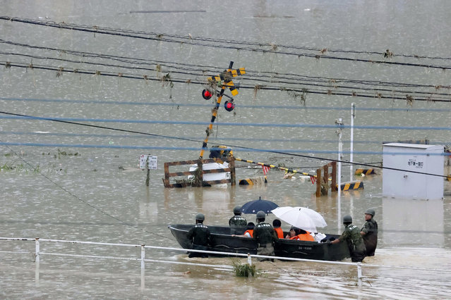 Japan Ground Self-Defense Force members evacuate people to a safer place by boat in Kuma village, Kumamoto prefecture, southwestern Japan, Sunday, July 5, 2020. Heavy rain in the Kumamoto region triggered flooding and mudslides Saturday and left dozens still being stranded at their homes and other facilities. (Photo by Kota Endo/Kyodo News via AP Photo)