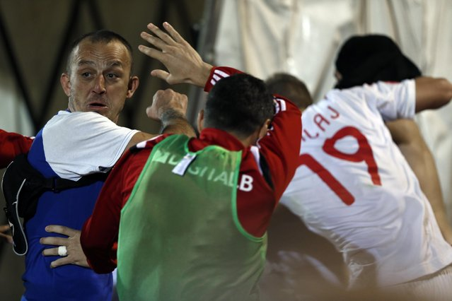 A Serbian national team supporter, left, attacks members of the Albanian national soccer team during the Euro 2016 Group I qualifying match between Serbia and Albania at the Partizan stadium in Belgrade, Serbia, Tuesday, October 14, 2014. (Photo by Marko Drobnjakovic/AP Photo)