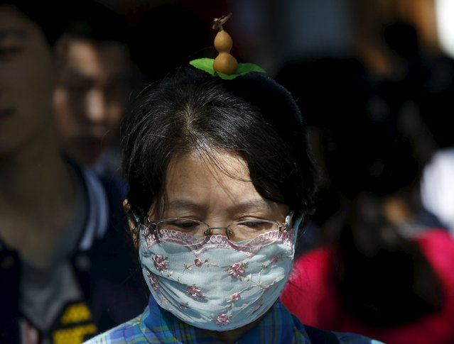 A woman wearing a calabash-like hairpin makes her way in Beijing, China, September 25, 2015. (Photo by Kim Kyung-Hoon/Reuters)