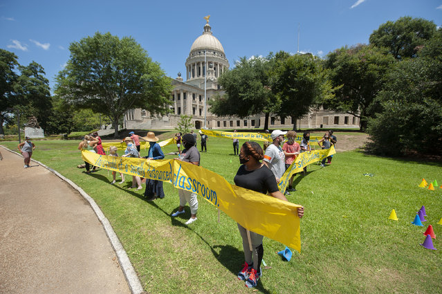 Teachers illustrate the average size of a Mississippi classroom and how only 11 students would be able to fit in it during a rally at the state Capitol in Jackson, Miss., Friday, July 17, 2020. The teachers, concerned about returning to school too soon amid rising COVID-19 numbers, are calling for delayed opening of the schools and for the legislature to fully fund education. (Photo by Barbara Gauntt/The Clarion-Ledger via AP Photo)