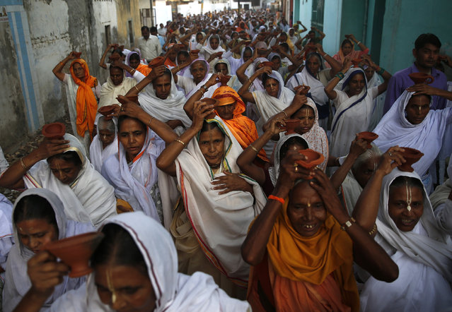 Widows, who have been abandoned by their families, carry earthen lamps on their heads as they arrive to offer prayers as part of Diwali celebrations organised by non-governmental organisation Sulabh International in Vrindavan, Uttar Pradesh October 21, 2014. (Photo by Ahmad Masood/Reuters)