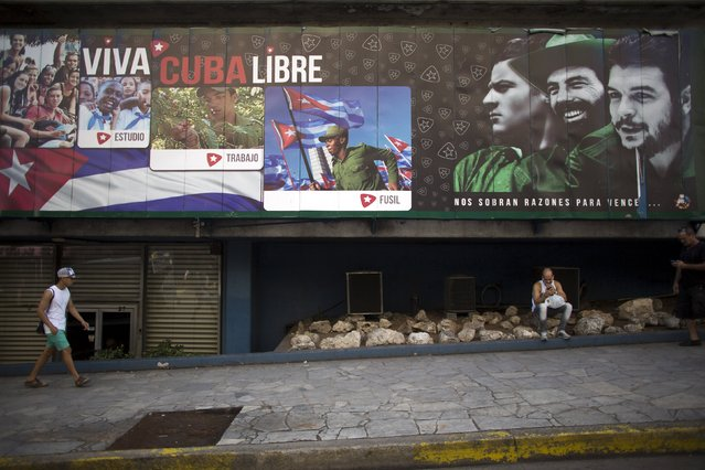 """Waiter Denis Sosa, 33, (R), uses his mobile phone to connect to the internet under an outdoor sign with images of Cuban late rebel revolutionary Camilo Cienfuegos (C), revolutionary hero Ernesto """"Che"""" Guevara (R) and co-founder of the first Communist Party of Cuba, Julio Antonio Mella, with messages reading """"Long live free Cuba"""", Havana, September 18, 2015. (Photo by Alexandre Meneghini/Reuters)"""