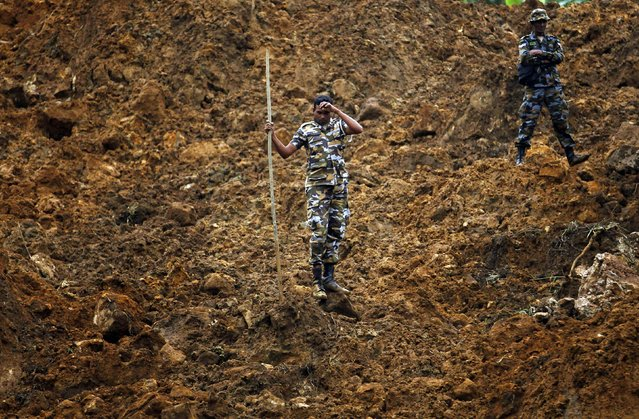 A member of a military rescue team pauses during search operations at the site of a landslide at the Koslanda tea plantation near Haldummulla October 30, 2014. (Photo by Dinuka Liyanawatte/Reuters)
