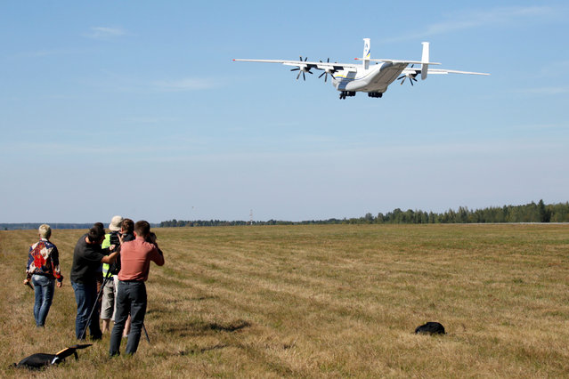 "Journalists watch Antonov An-22A ""Antei"" (Antheus), believed to be the world's largest turboprop-powered aircraft, taking off from the tarmac at the Antonov aircraft plant before the first commercial flight after its renovation in the settlement of Hostomel outside Kiev, Ukraine, September 8, 2016. (Photo by Valentyn Ogirenko/Reuters)"
