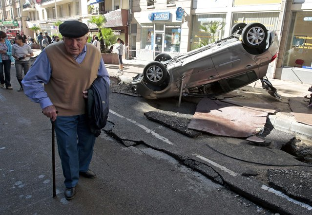 A man walks past an overturned car in the street that was damaged in flooding caused by torrential rain in Cannes, France, October 4, 2015. (Photo by Eric Gaillard/Reuters)