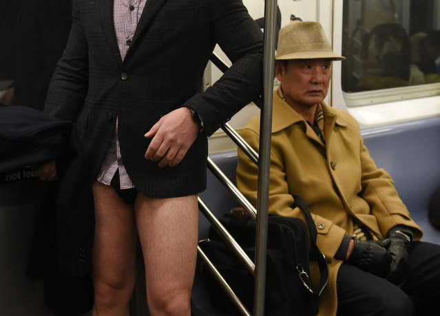 """Participants in the 17th Annual """"No Pants Subway Ride"""" travel in the New York City subway on January 7, 2018 in New York. (Photo by Timothy A. Clary/AFP Photo)"""