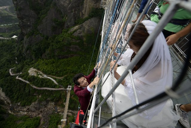 Newlyweds take wedding photos hanging from bridge, Yueyang, Hunan province, China on August 9, 2016. (Photo by Top Photo Corporation/Rex Features/Shutterstock)