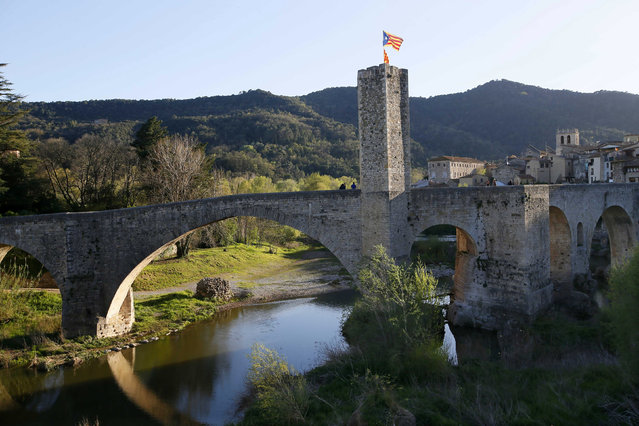 A Catalan separatist flag, known as Estelada, flutters on the top of the medieval bridge in the old city of Besalu, near Girona, April 5, 2014. (Photo by Gustau Nacarino/Reuters)