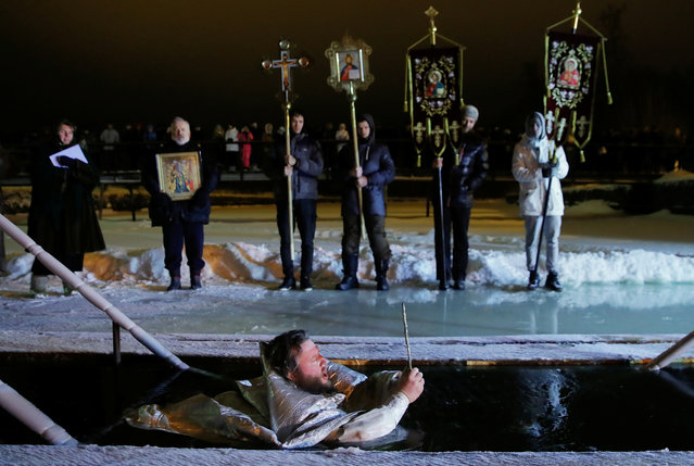 A priest takes a dip into the water during Orthodox Epiphany celebrations in the village of Drachevo, outside Moscow, Russia on January 19, 2018. (Photo by Maxim Shemetov/Reuters)