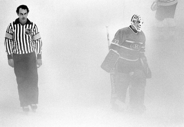 Referee Bryan Lewis and Montreal Canadiens Richard Sevigny skate through the fog at the Boston Garden Thursday night, October 13, 1983. Warm, humid weather helped create the fog that interrupted the Boston-Montreal hockey game. (Photo by Mike Kullen/AP Photo)