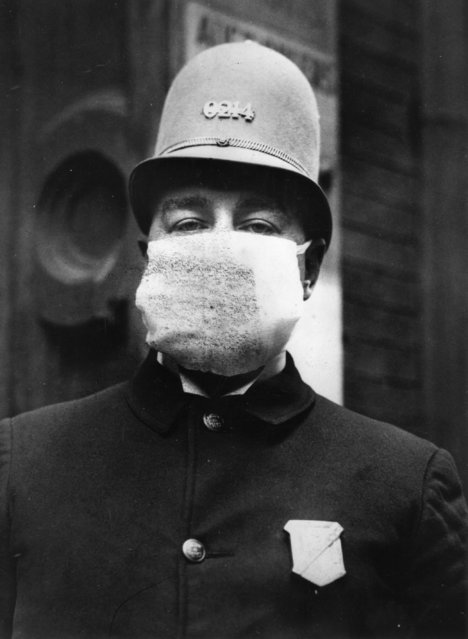 "An American policeman wearing a ""Flu Mask"" to protect himself from the outbreak of Spanish flu following World War I, 1918. (Photo by Topical Press Agency/Getty Images)"