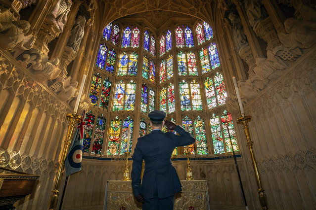 Flying Officer James Buckingham salutes The Battle of Britain memorial window inside Westminster Abbey, the stained glass window by Hugh Easton that contains the badges of the fighter squadrons that took part in the Battle, during a service to mark the 80th anniversary of the Battle of Britain at Westminster Abbey, London, Sunday, September 20, 2020. (Photo by Aaron Chown/Pool Photo via AP Photo)