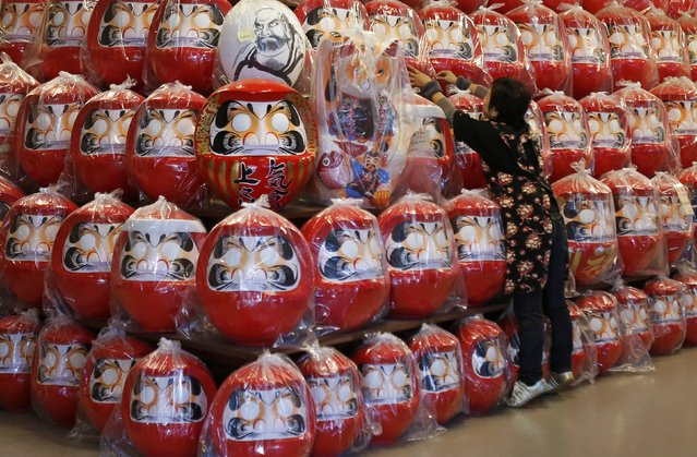 """A staff adjusts the positions of Daruma dolls ,  which is believed to bring good luck, displayed at Daruma shop  """"Daimonya"""" in Takasaki, northwest of Tokyo November 23, 2014. (Photo by Yuya Shino/Reuters)"""