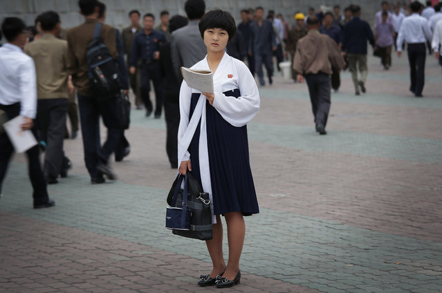 A North Korean student pauses to study as other people make their way to work during morning rush hour on Wednesday, September 28, 2016, in Pyongyang, North Korea. North Korea's capital is still a pretty quiet place compared to most urban centers around the world, but it gets its start early, and orderly. (Photo by Wong Maye-E/AP Photo)