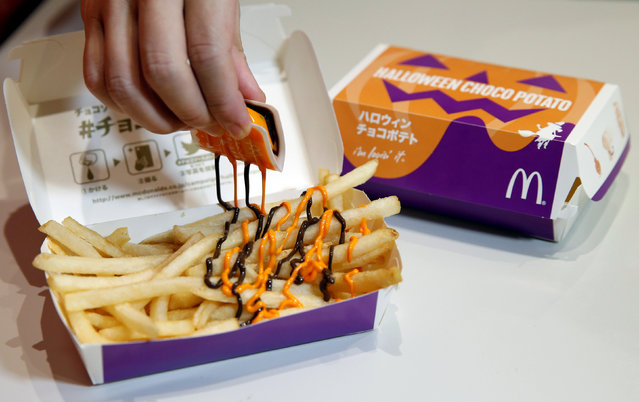 "An employee of McDonald's Japan puts pumpkin and choco sauce on a McFry Potato to demonstrate their company's ""Halloween Choco Fries – Pumpkin & Choco Sauce"" in Tokyo, Japan, September 29, 2016. (Photo by Toru Hanai/Reuters)"