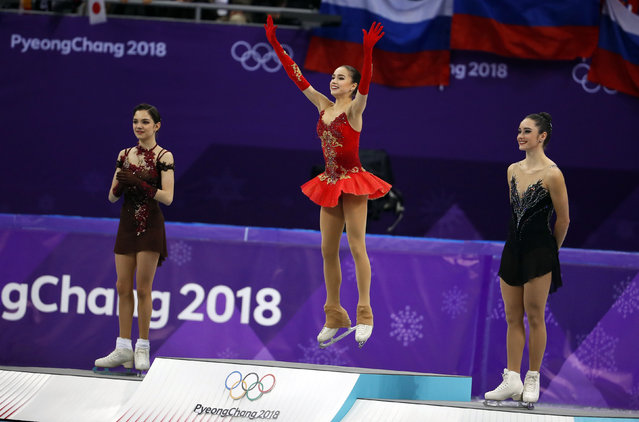 (L- R) Silver medallist Russia' s Evgenia Medvedeva, gold medallist Russia' s Alina Zagitova and bronze medallist Canada' s Kaetlyn Osmond celebrate on the podium during the venue ceremony after the women' s single skating free skating of the figure skating event during the Pyeongchang 2018 Winter Olympic Games at the Gangneung Ice Arena in Gangneung on February 23, 2018. (Photo by Phil Noble/Reuters)