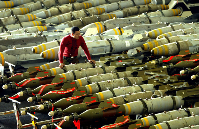 An aviation ordnance man observes rows of bombs on the hangar bay of the USS Kitty Hawk aircraft carrier in the northern Gulf, on March 30, 2003. The carriers airwing flew 104 total sorties over Iraq on March 29, and dropped bombs on targets including air defense sites, a train loaded with tanks and a surface-to-air missile site. (Photo by Paul Hanna/Reuters/The Atlantic)