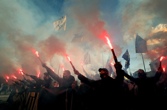 """Activists of different nationalists parties burn flares during the march with the slogan """"The battle to collaborators!"""" in downtown Kiev, Ukraine, 14 October 2020.  Ukrainians mark the """"Day of defender of Motherland"""" and the 78th anniversary of the Ukrainian Insurgent Army (UPA) creation, which fought for Ukrainian independence against the Soviet Red Army and the Nazis during the Second World War. (Photo by Sergey Dolzhenko/EPA/EFE)"""