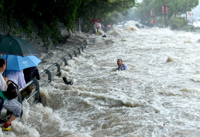 A tourist struggles in the water, before standing up and wading away, after a wave strengthened by the influence of Typhoon Dujuan hit a river bank in Hangzhou, Zhejiang province, September 29, 2015. (Photo by Reuters/China Daily)