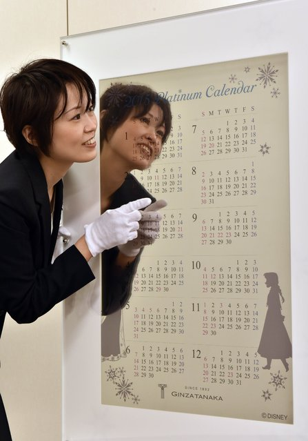 An employee of Japanese jeweler Tanaka Kikinzoku Jewelry displays a pure platinum made calendar for 2015 at the company's Ginza shop in Tokyo on December 3, 2014. The calendar measuring 77cm x 50cm and weighing 10 kilograms is priced at 100 million yen (840,000 USD). (Photo by Yoshikazu Tsuno/AFP Photo)