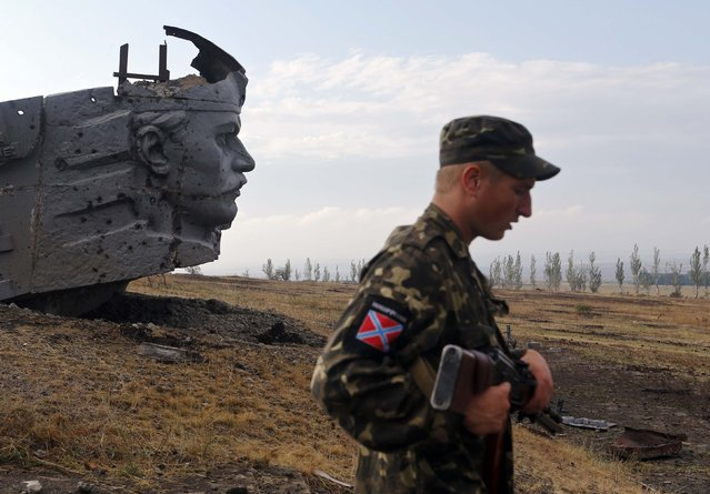 A Pro-Russian separatist stands near the damaged war memorial at Savur-Mohyla, a hill east of the city of Donetsk, in this August 28, 2014 file photo. (Photo by Maxim Shemetov/Reuters)