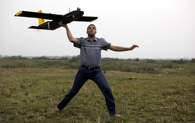 Remo Peduzzi, managing director of ResearchDrones LLC Switzerland, prepares to fly a drone at the Kaziranga National Park at Kaziranga in Assam state, India, on April 8, 2013. Wildlife authorities used drones on Monday for aerial surveillance of the sprawling natural game park to protect the one-horned rhinoceros from armed poachers. The drones are equipped with cameras and will be monitored by security guards, who find it difficult to guard the whole 185-square mile reserve. (Photo by Anupam Nath/Associated Press)