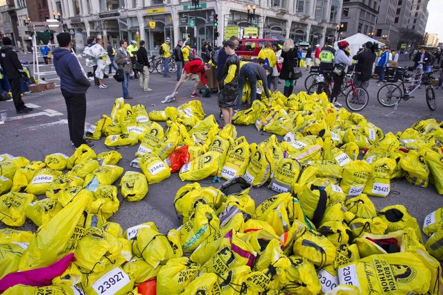 Volunteers organize participants for belongings for collection after two explosions interrupted the running of the Boston Marathon in Boston, Massachusetts April 15, 2013. (Photo by Dominick Reuter/Reuters)