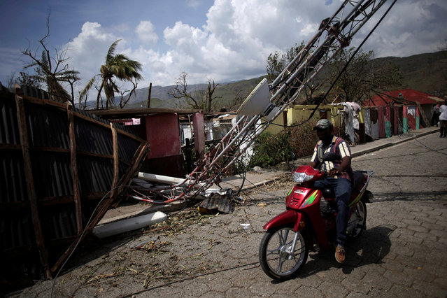A man rides a motorbike next to an antenna down by Hurricane Matthew in Les Anglais, Haiti, October 10, 2016. (Photo by Andres Martinez Casares/Reuters)